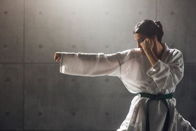 Концепция боевых искусств. молодая женщина в кимоно практикует карате