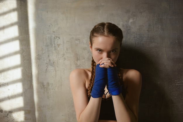 武道、戦闘、ボクシング、キックボクシング。戦いの準備ができて、包帯で包まれた手を握り締めて自信を持ってスポーティな女の子の肖像画をクローズアップ