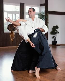Istruttori di arti marziali che si allenano nella sala pratica