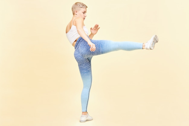 Martial arts, karate and kung fu concept. full length image of tough young blonde woman mma fighter in top, leggings and sneakers training indoors kicking invisible enemy with one leg outstretched