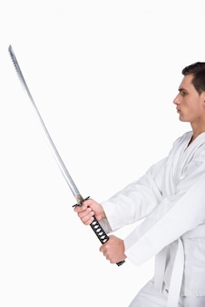 A martial arts man is standing with a sword.