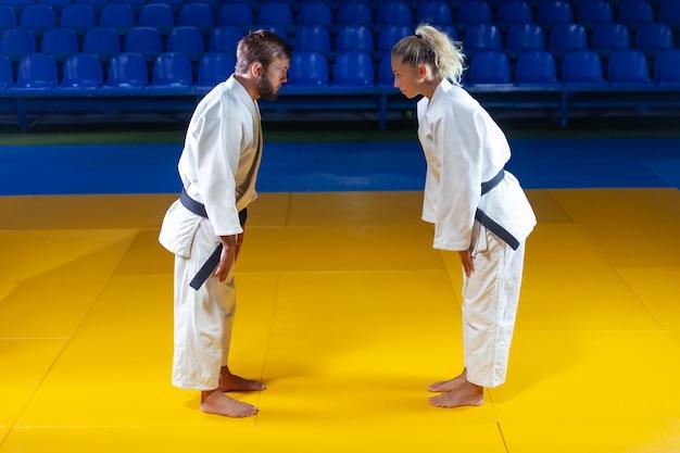 Боевые искусства. щадящие портнеры. спорт мужчина и женщина приветствуют друг друга перед боем в спортивном зале