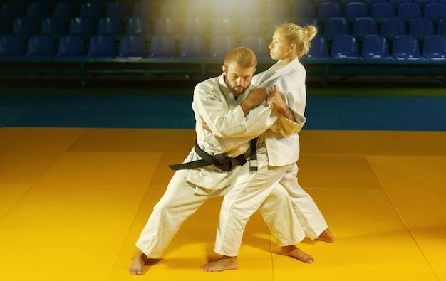 Боевые искусства. щадящие портнеры. спорт мужчина и женщина в белом кимоно тренируются в бросках и захватах дзюдо в спортивном зале