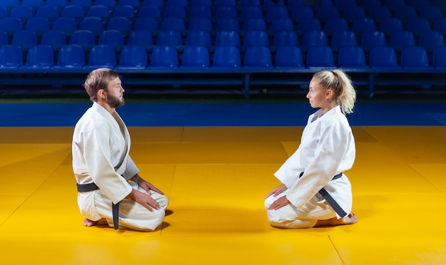 Martial arts. sparing portners. sport man and woman greet each other while sitting in sports hall