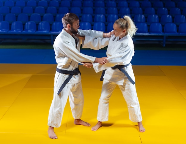 Martial arts. sparing portners. sport man and woman in white kimono train judo captures in the sports hall