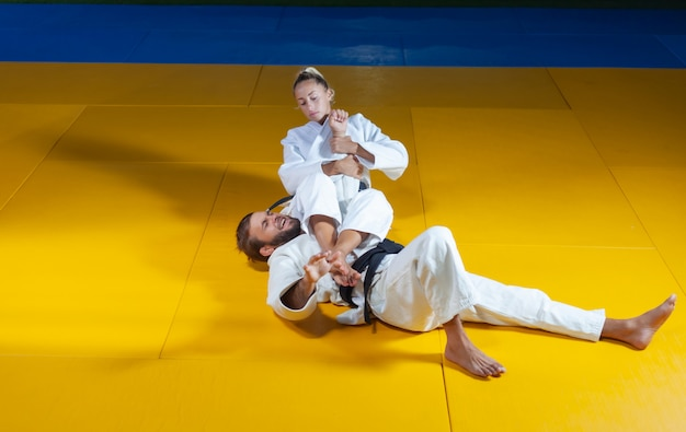 Martial arts. sparing portners. sport man and woman in white kimono train judo throws and captures in the sports hall