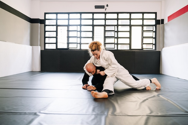 Martial arts training such as judo or karate with kimonos practicing techniques on the gym mat all wearing face masks due to the covid 19