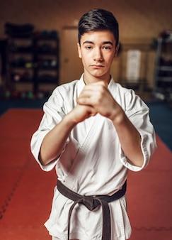 Боевые искусства, молодой боец в белом кимоно и черном поясе в знак уважения, тренировки в помещении