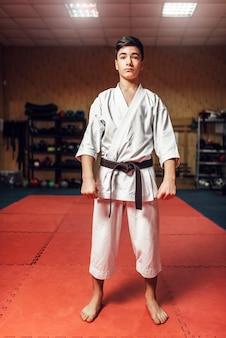Боевые искусства, молодой боец в белом кимоно и черном поясе на тренировке в тренажерном зале