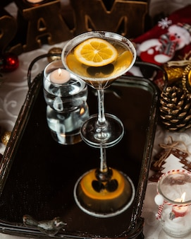 A martini glass of alcohol drink with black olive and lemon slice
