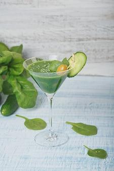 밝은 파란색 나무 배경에 신선한 녹색 시금치와 오이 스무디로 채워진 마티니 유리. 무알코올 음료. 건강에 좋은 음식과 채식주의 개념.
