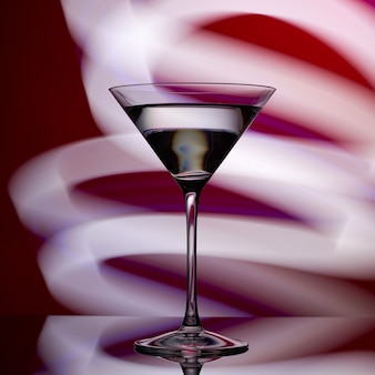 Martini glass on a red with white lights.