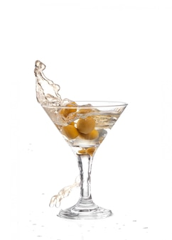 A martini glass on a white background; the water ripples and splashed as a green spanish olive with pimento is dropped into the glass; horizontal format