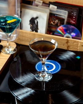 A martini glass with dark colored cocktail placed on vinyl record