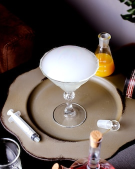 A martini glass with smoked cocktail placed next to needle and conical flask with orange juice