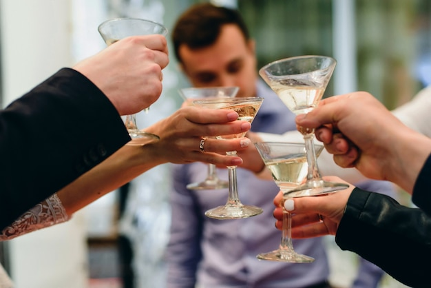 Martini glasses in hands of a group of friends celebrating the wedding