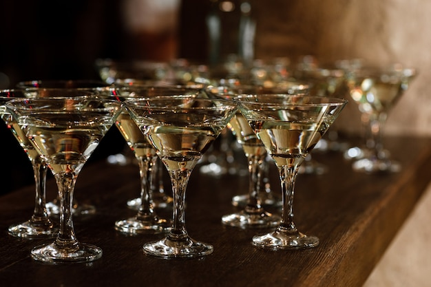Martini glasses stand on a wooden stand.
