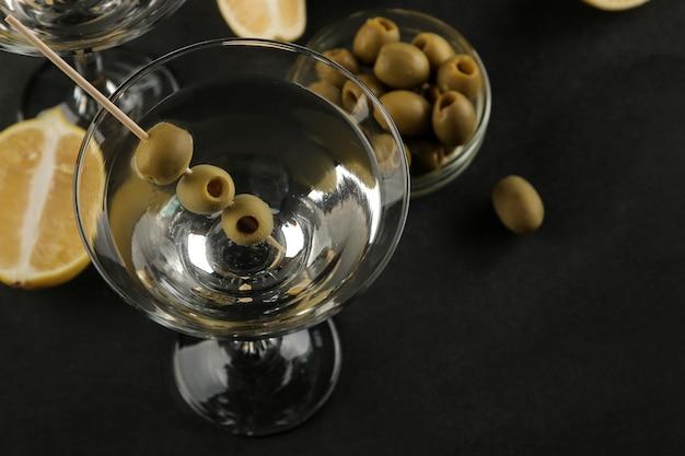 黒いテーブルの串にグリーンオリーブとガラスのワイングラスのマティーニ。カクテル。バー
