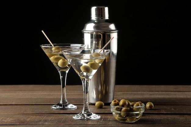 茶色の木製テーブルの串にグリーンオリーブとガラスのワイングラスのマティーニ。カクテル。バー