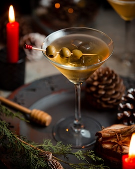 Martini with green olives in christmas background.