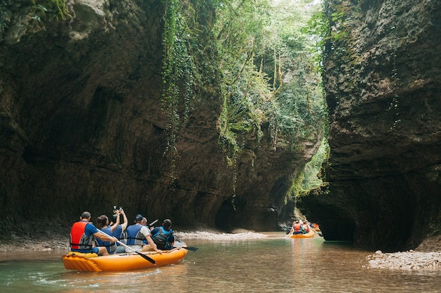 Martvili/georgia. a group of tourists floating in a rubber boat on the river martvili canyon