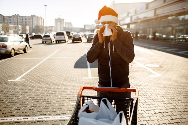 メアリークリスマス&明けましておめでとうございます。ハンカチと赤いサンタクロースの男。病気の女の子は鼻水が出ています。女性モデルが風邪の治療法を作るスーパーマーケットで購入する