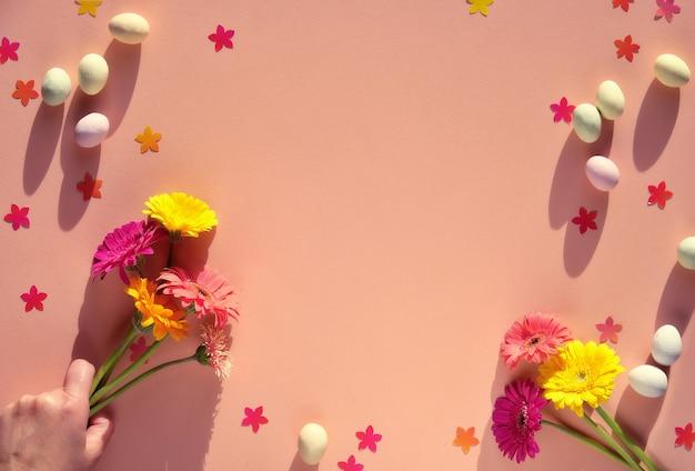 Марципановые пасхальные яйца, цветы герберы, конфетти на оранжевой бумаге