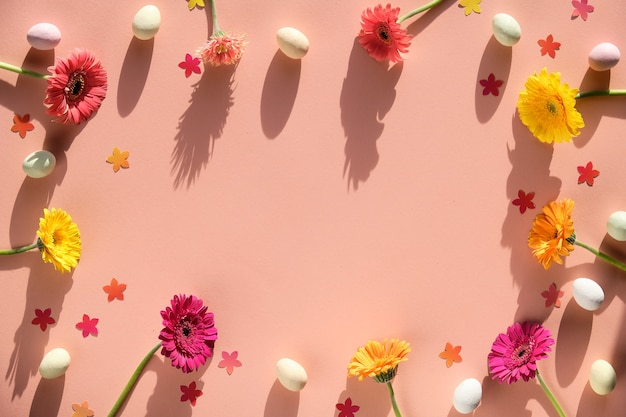 Марципановые пасхальные яйца, цветы герберы и конфетти на теплой розовой бумаге.