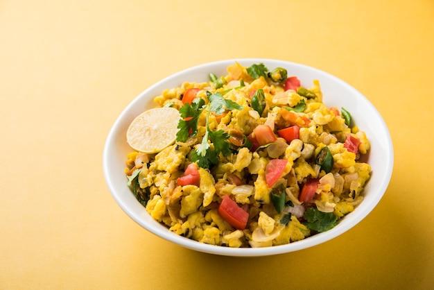 Масала анда бурджи или острая индийская яичница, популярная уличная еда в мумбаи. подается в белой посуде, изолированной на мрачном фоне. выборочный фокус
