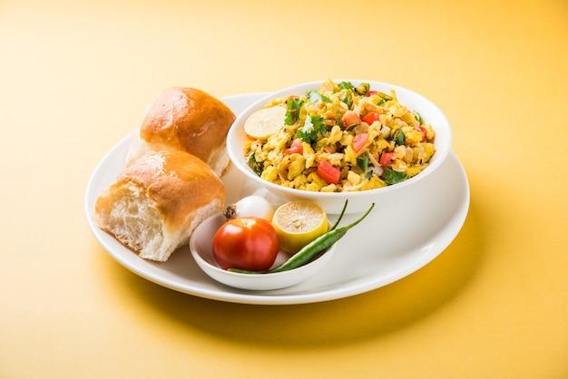 Масала анда бурджи или острая индийская яичница с жареным хлебом или булочка или пав, популярная уличная еда в мумбаи. подается в белой посуде на мрачном фоне. выборочный фокус