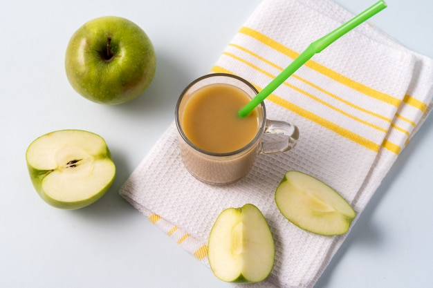 Masala chai tea in a glass cup and fresh apples over white background.