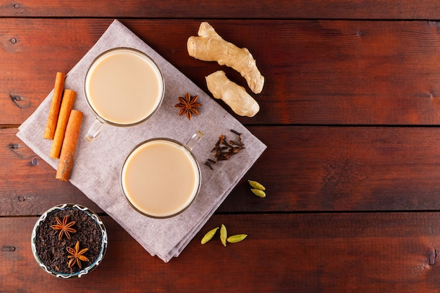 Masala chai tea on linen napkin. traditional indian drink - masala tea with spices on a wooden background.