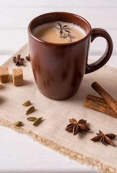Masala chai tea in a mug and kitchen herbs, over white table