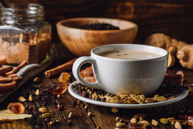 Masala chai in white cup with different spices