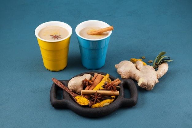 Masala tea in colored ceramic glasses and ingredients.