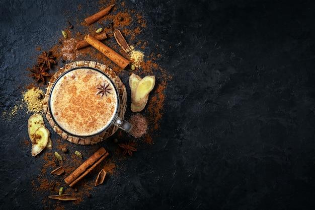 青いコンクリートのテーブルにシナモンとアニスのマサラティー。コンクリートテーブルの上のスパイスとマサラ茶のカップ。上面図。