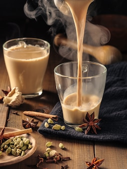 Masala tea with spices is poured into glass mugs on a wooden table.