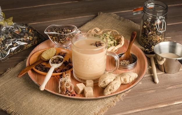 Чай масала со специями на деревянной поверхности, согревающий напиток из индии
