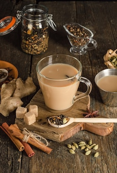 Masala tea with spices on a wooden background, a warming drink from india