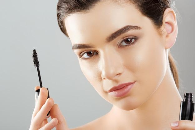 아름 다운 젊은 여자의 마스카라 근접 촬영 뷰티 메이크업으로 얼굴, 화장품 브러시로 마스카라를 적용하는 신선한 부드러운 피부.