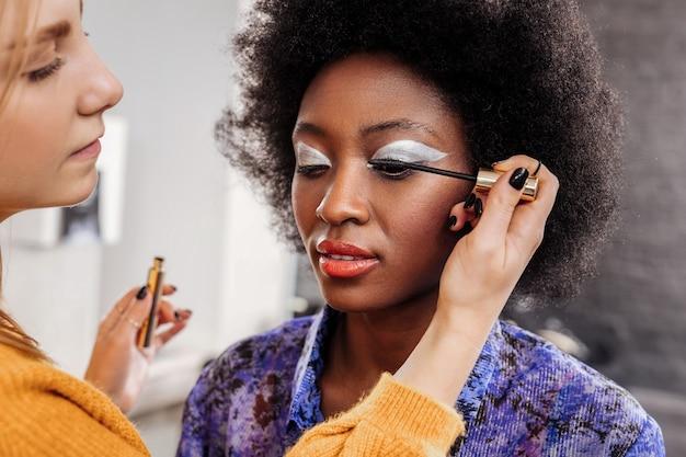 Mascara. fair-haired young stylist wearing black nail polish putting mascara on models eyelashes