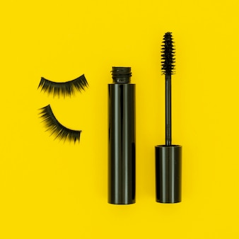 Mascara and fake lashes on yellow background