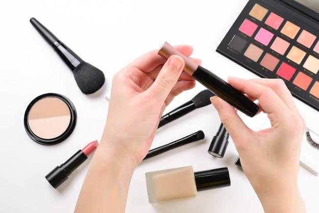 Тушь в руках женщины. профессиональные продукты для макияжа с косметическими продуктами, тональным кремом, губной помадой, тенями для век, ресницами, кистями и инструментами.