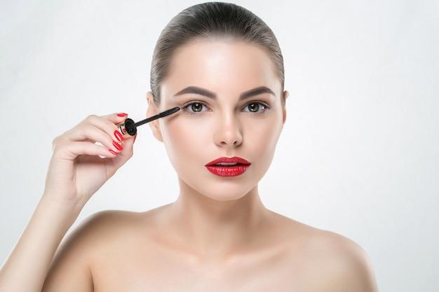 붉은 입술과 매니큐어 손톱 흰색 절연 마스카라 메이크업 여자 얼굴. 스튜디오 촬영.