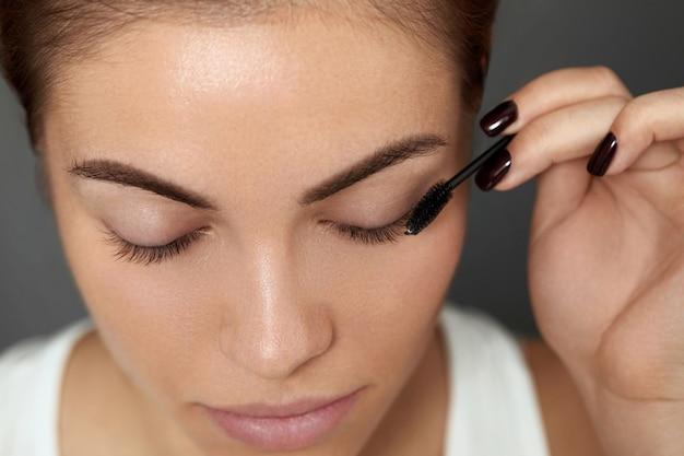 Mascara. woman applying black mascara on eyelashes with makeup brush. beautiful young woman face with natural eyebrows and eyelashes.