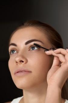 Тушь. женщина наносит черную тушь на ресницы с помощью кисти для макияжа