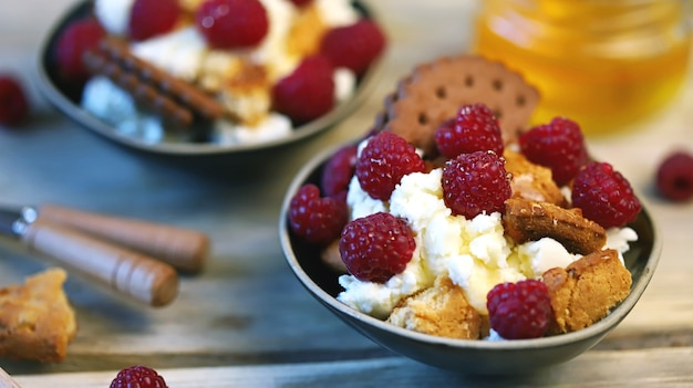 Mascarpone dessert with raspberries and biscuits in bowls.