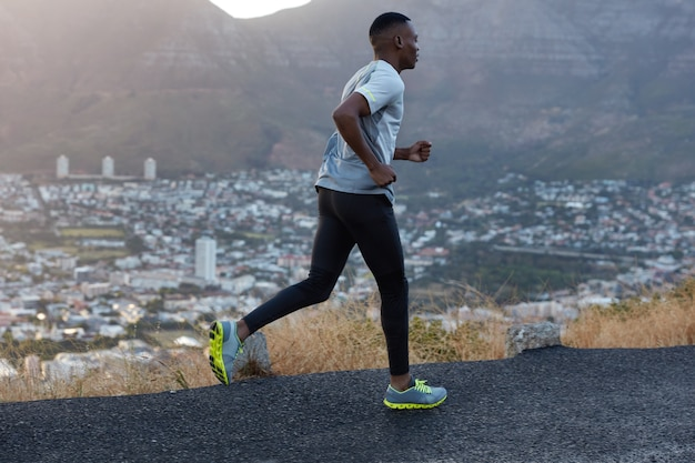Masculine athlete person with slim healthy body dressed in sportsclothes, poses in profile, runs on high speed, participates in marathon, photographed against beautiful city view, mountain scenery