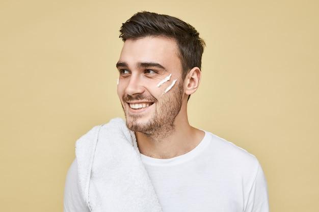 男性的な美しさの概念。彼の顔にクリームを剃った後、肩にタオルを持って、笑顔で目をそらして、朝のバスルームでポーズをとっている剛毛を持つ幸せな魅力的な若い白人男性