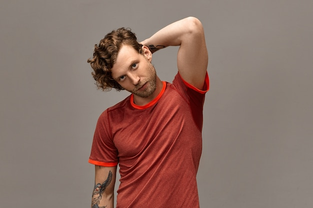 Masculine beauty, healthy active lifestyle and people concept. portrait of confident good looking male runner with trimmed beard, curled hair and tattoo posing isolated, holding hand behind his head